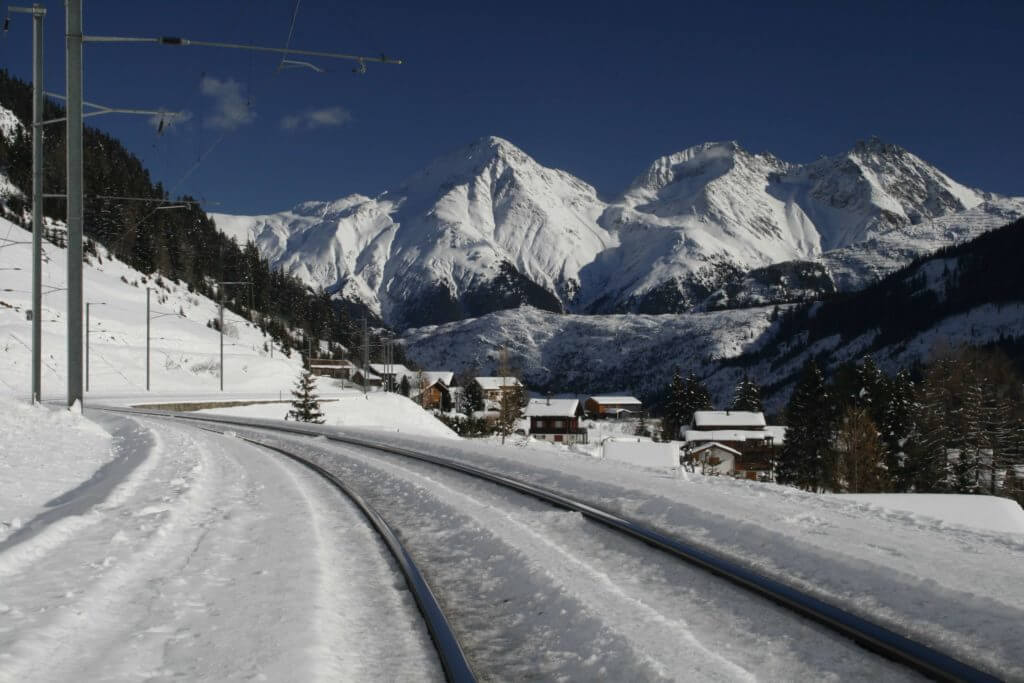 Train tracks through snow covered mountains