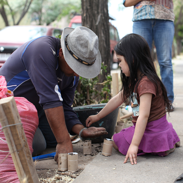 Gabriel teaching how to plant seeds at a Sustento market day