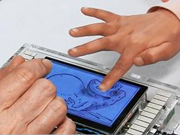 Cette photo montre la main d'un enfant qui touche un petit écran sur lequel est affiché un petit animal (style bande dessinée). Il s'agit d'un prototype de livre tactile.