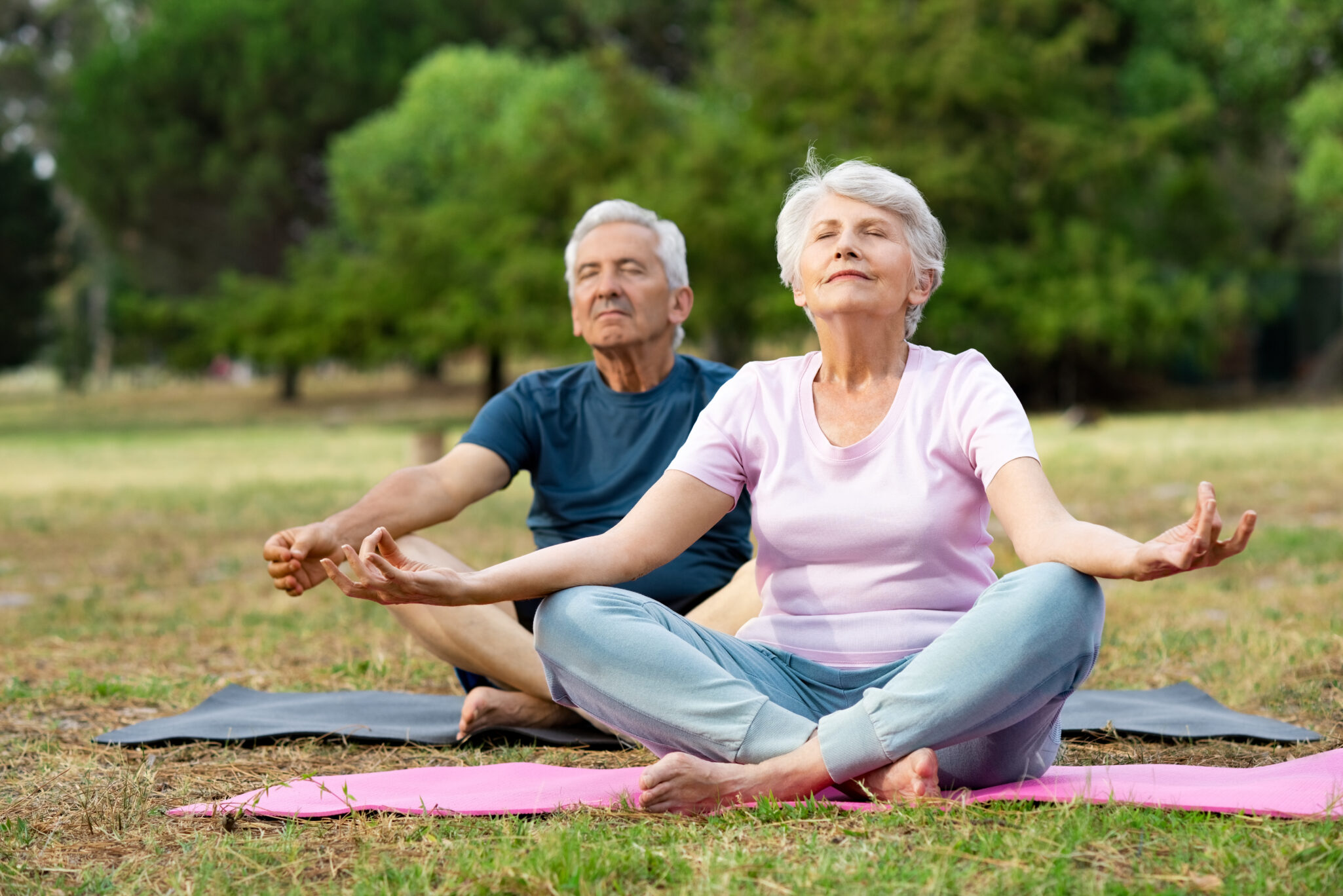 Senior man and elderly woman meditating sitting in lotus position at park with closed eyes.