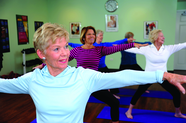 a group of senior women taking a yoga class at their senior living community