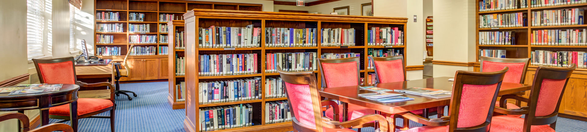 a library inside of a senior living community with tables and chairs to sit at