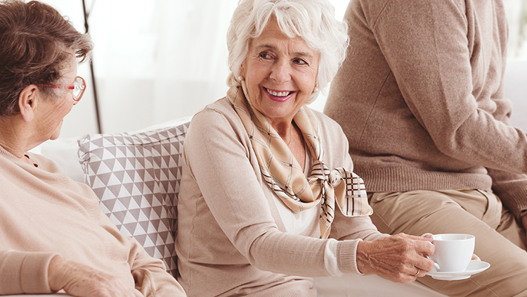 three senior women enjoying coffee while talking with one another