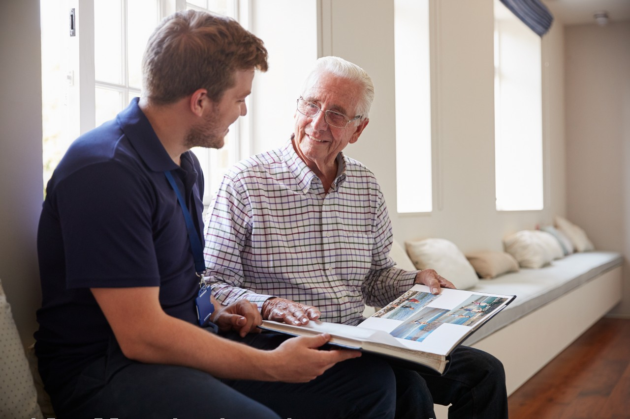 senior man in memory care looks through a photo album with health care worker