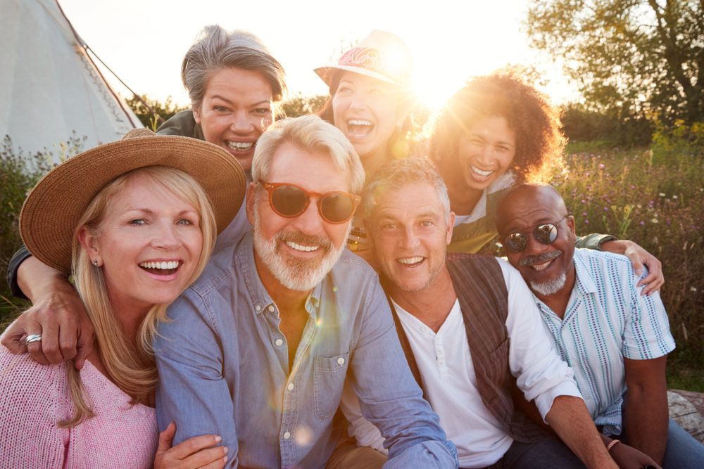 A group of people in their 50s pose for a photo outside at sunset