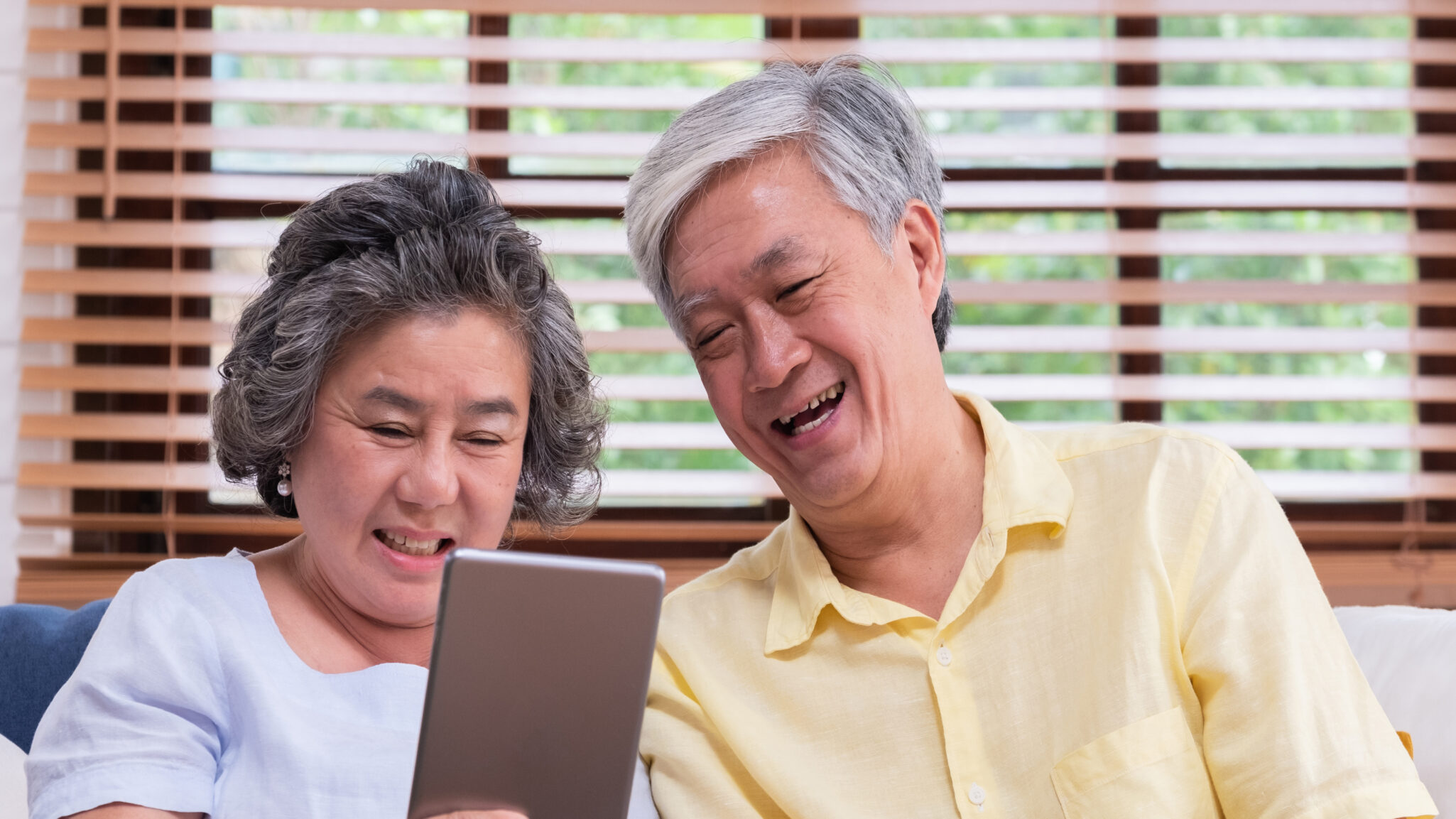 a senior couple researching senior living options on their tablet