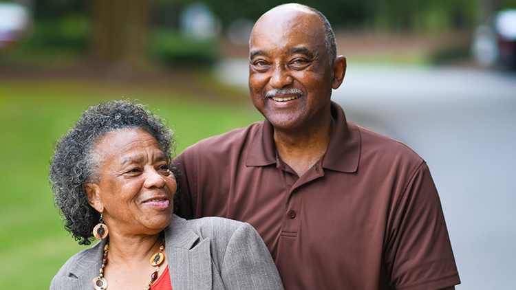 a senior couple smiling and posing for a photo
