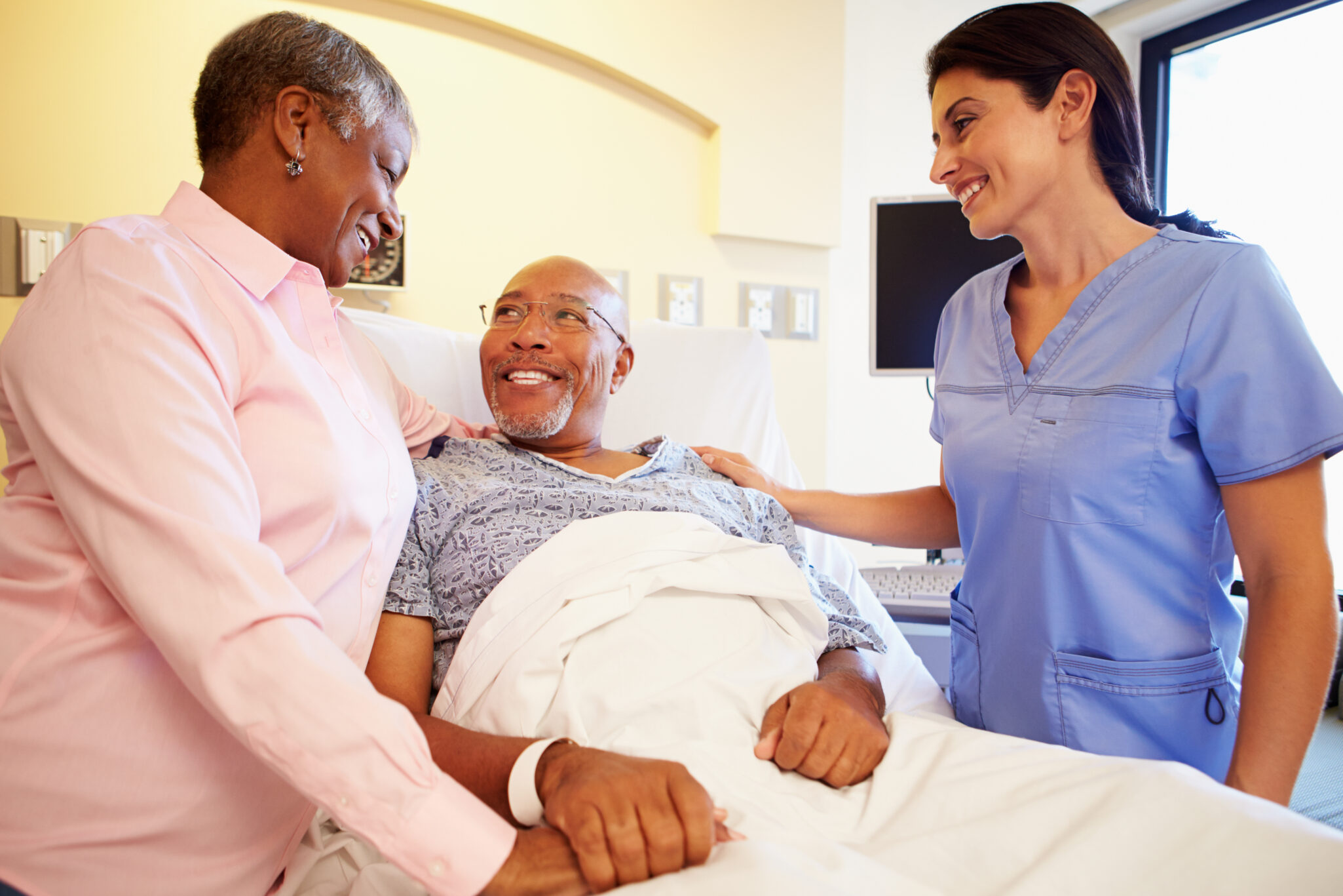 A health care professional checks on a senior man in a skilled nursing facility who is talking with his wife