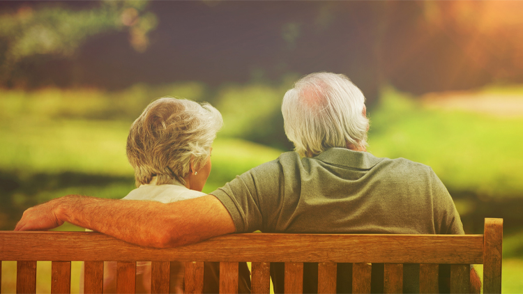a senior couple sitting on a bench outside