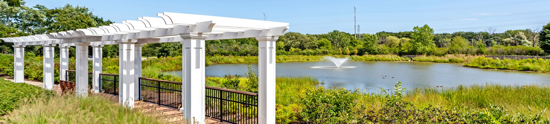 a covered walkway next to a pond with a fountain