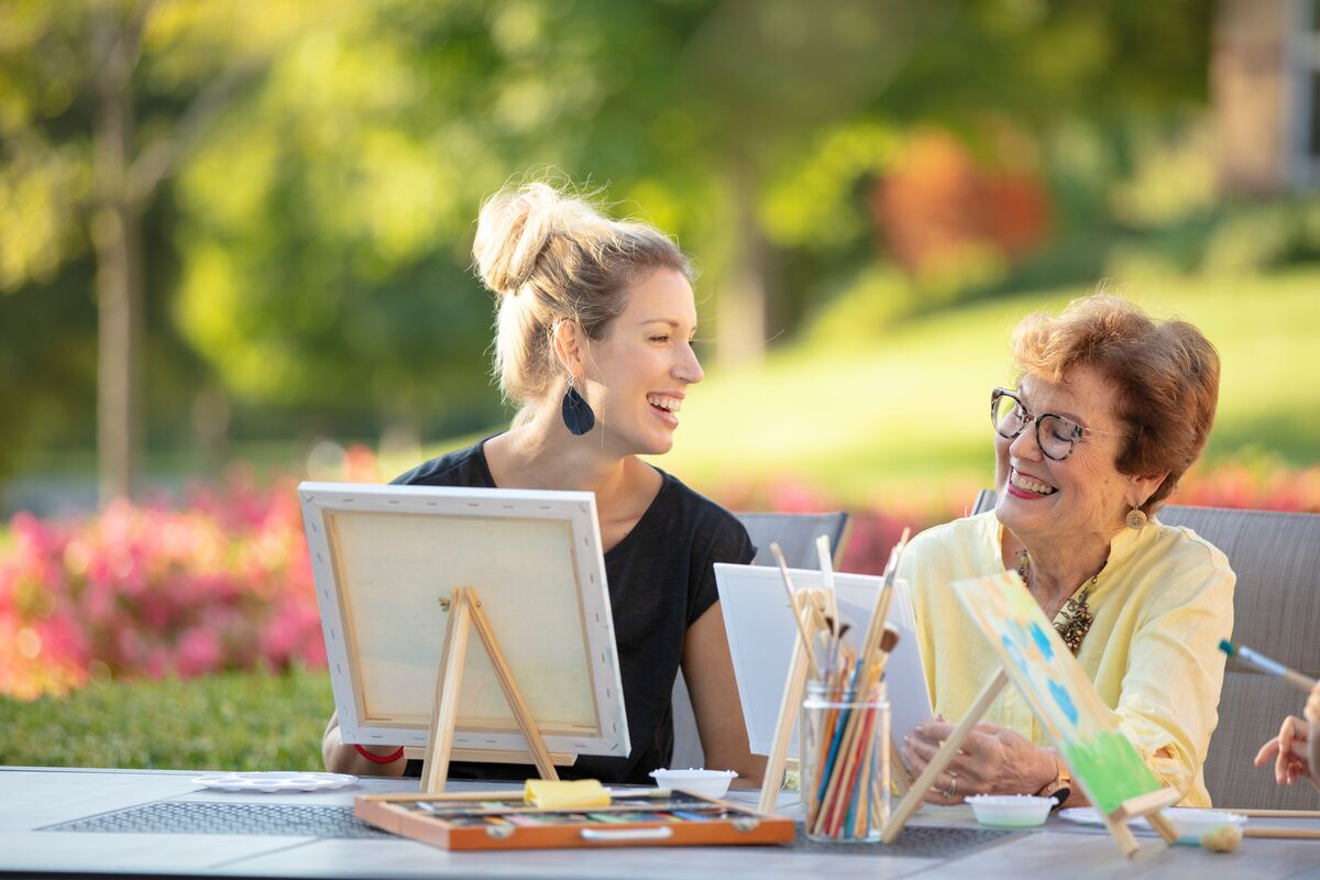 College student happily painting with a senior citizen