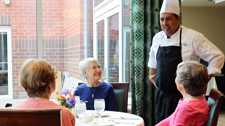 a group of senior women talking to the chef at their senior living community