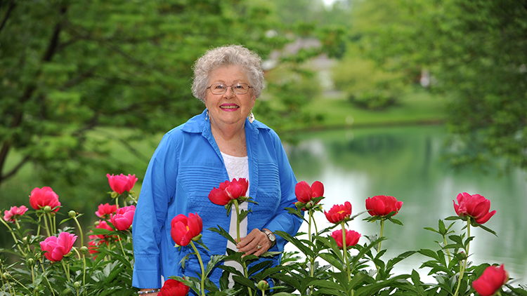a senior woman posing with flowers in front of a body of water