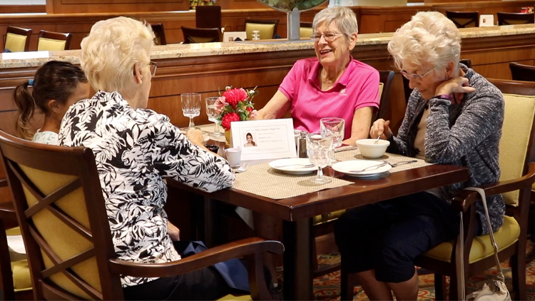 a group of senior women enjoying a meal in the dining area of The Moorings at Arlington Heights senior living community