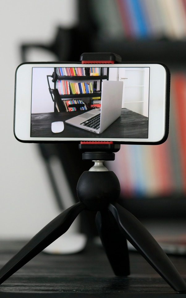 Image: Smartphone mounted sideways in a tripod stand, capturing video