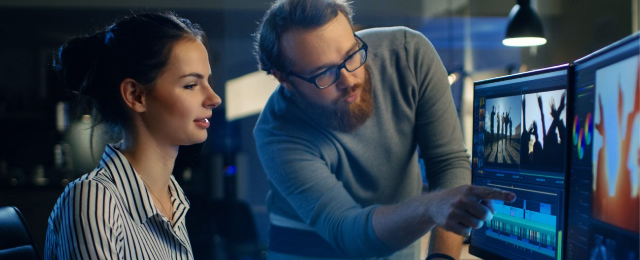 Digital Entertainment & Interactive - Man and woman working on editing visual effects on a computer in a dark studio setting