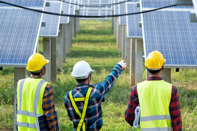 Green Economy - Three men with hard hats looking at solar panels, a green jobs in action