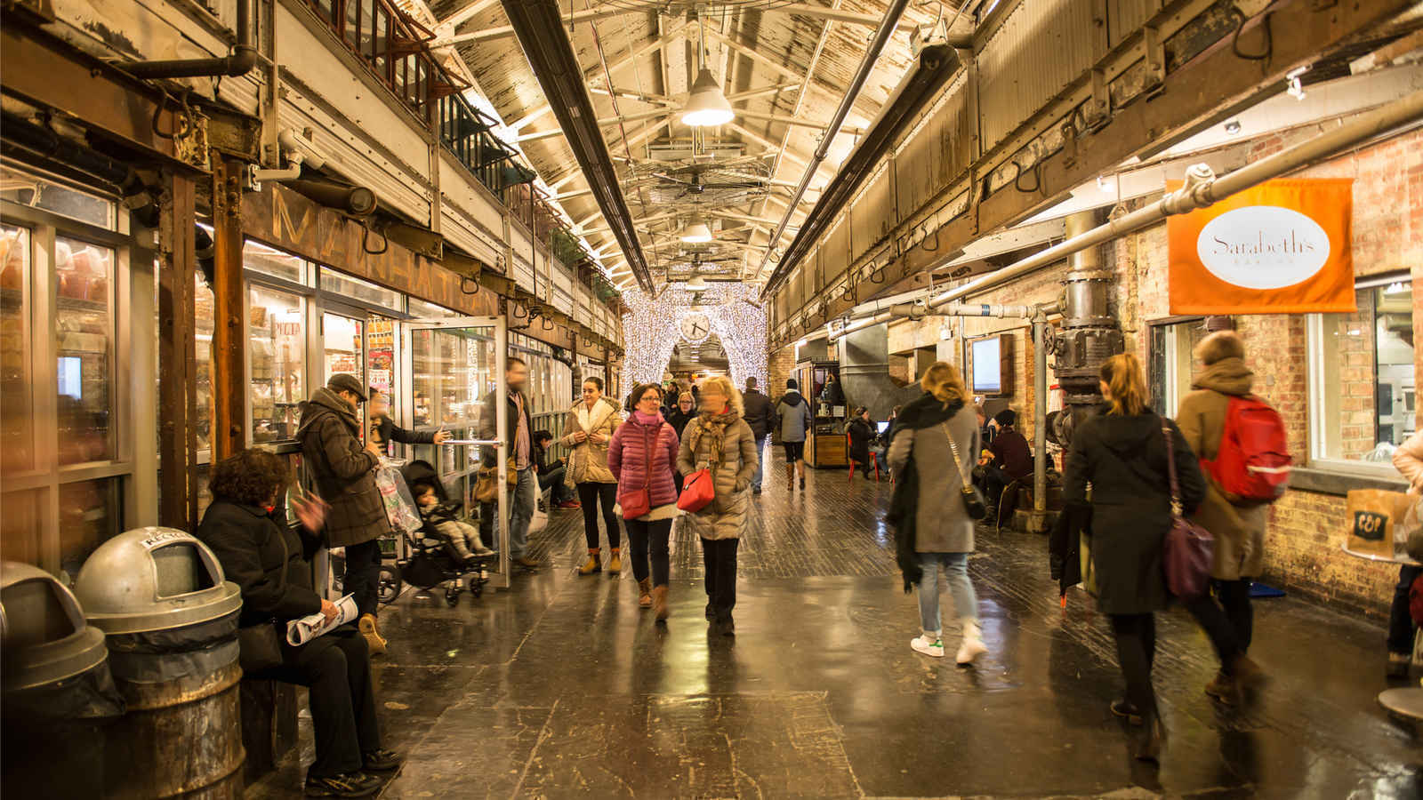 People browsing shops and restaurant storefronts inside Chelsea Market