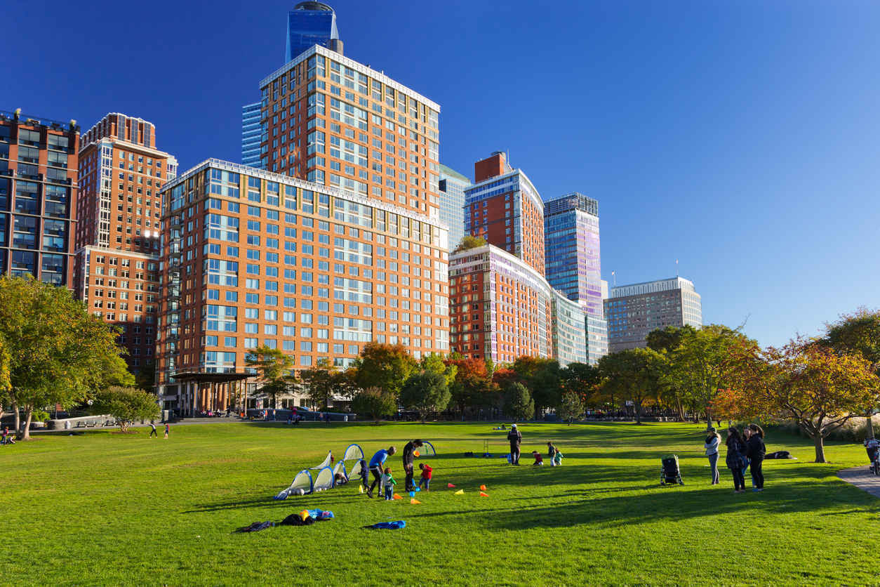 People relaxing on lawn in front of residential apartment buildings in Battery Park City