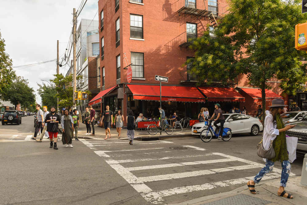 Stores and restaurants on tree-lined Bedford Ave, Williamsburg, Brooklyn