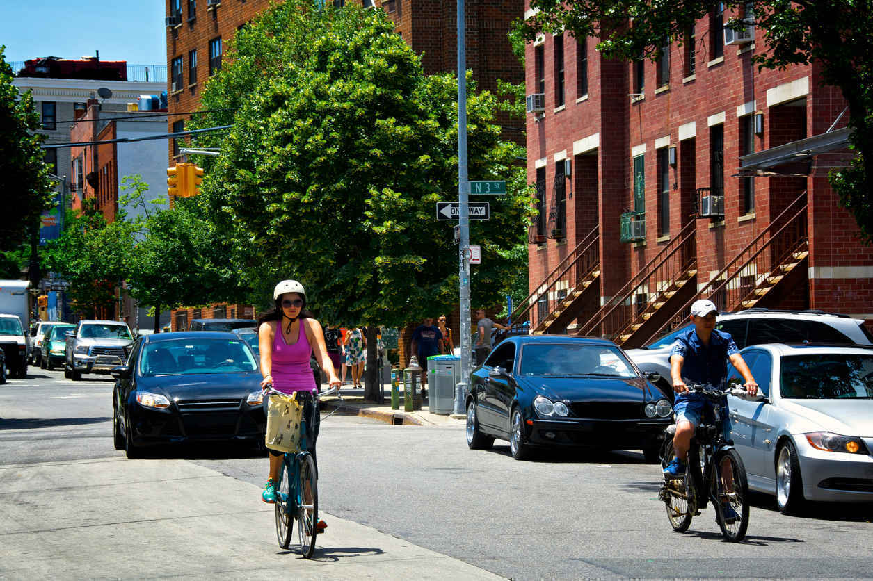 People riding bikes on tree-lined street in Williamsburg Brooklyn