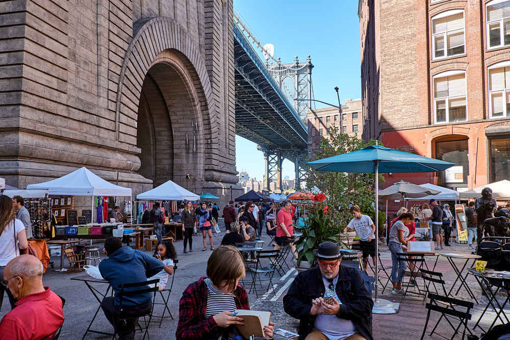 People shopping, sitting and relaxing at the DUMBO Flea  market in Brooklyn