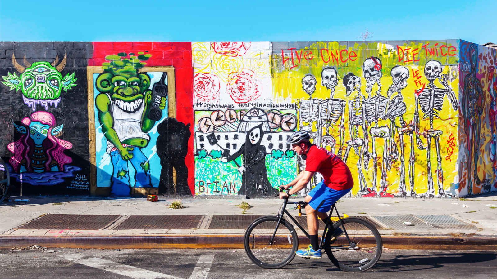 Man riding bike past graffiti art mural in Bushwick Brooklyn