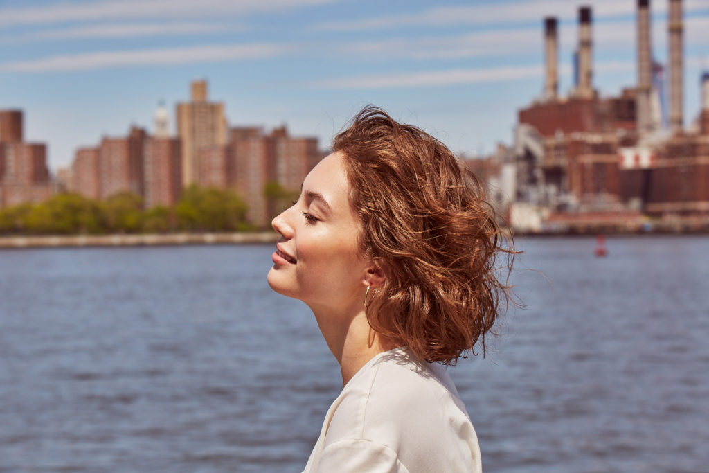 Side profile of a smiling woman in front of the water with background view of the city.