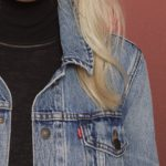 Woman with blonde hair, denim jacket, and black turtle neck.
