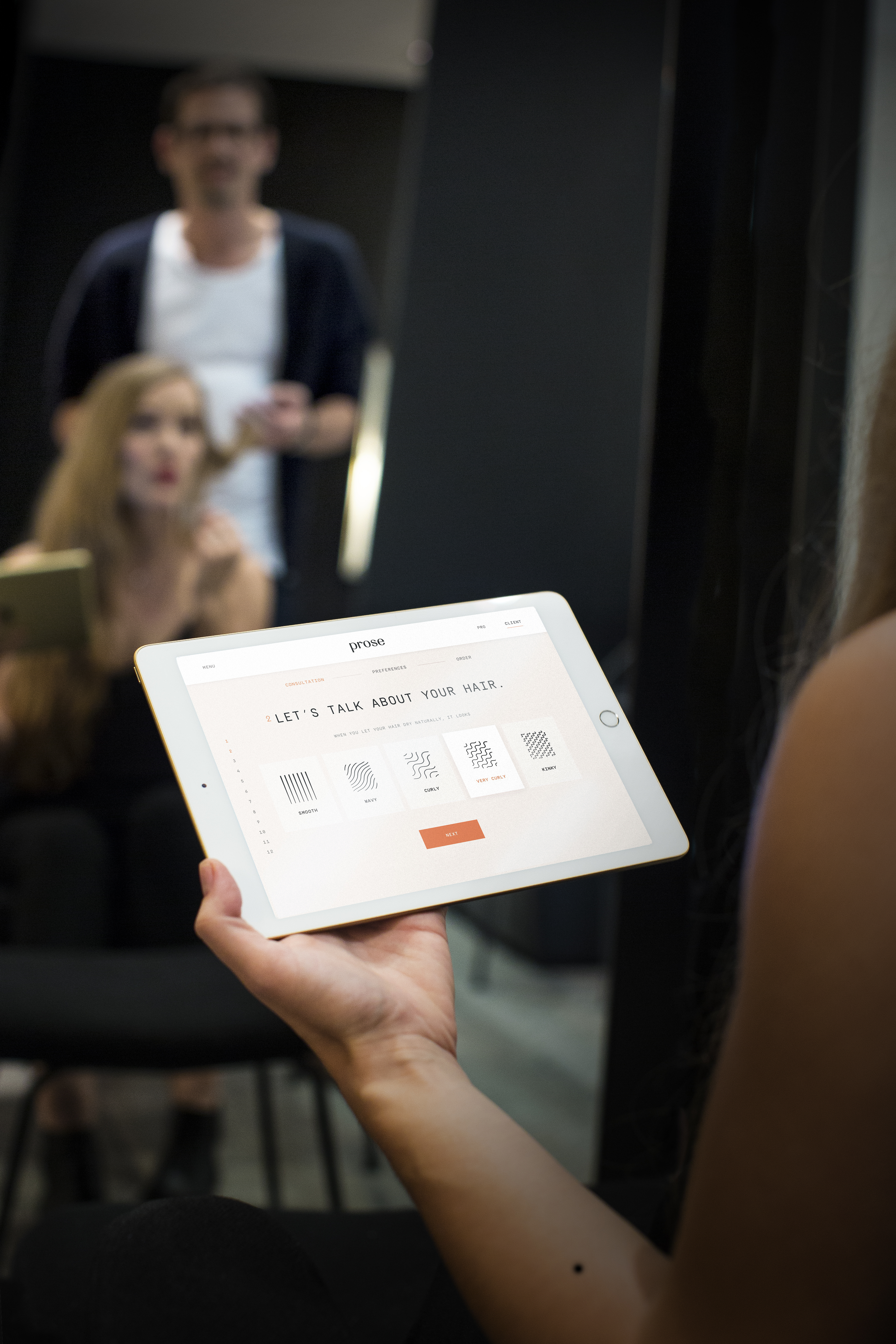 Woman at a hair consultation holding an iPad.