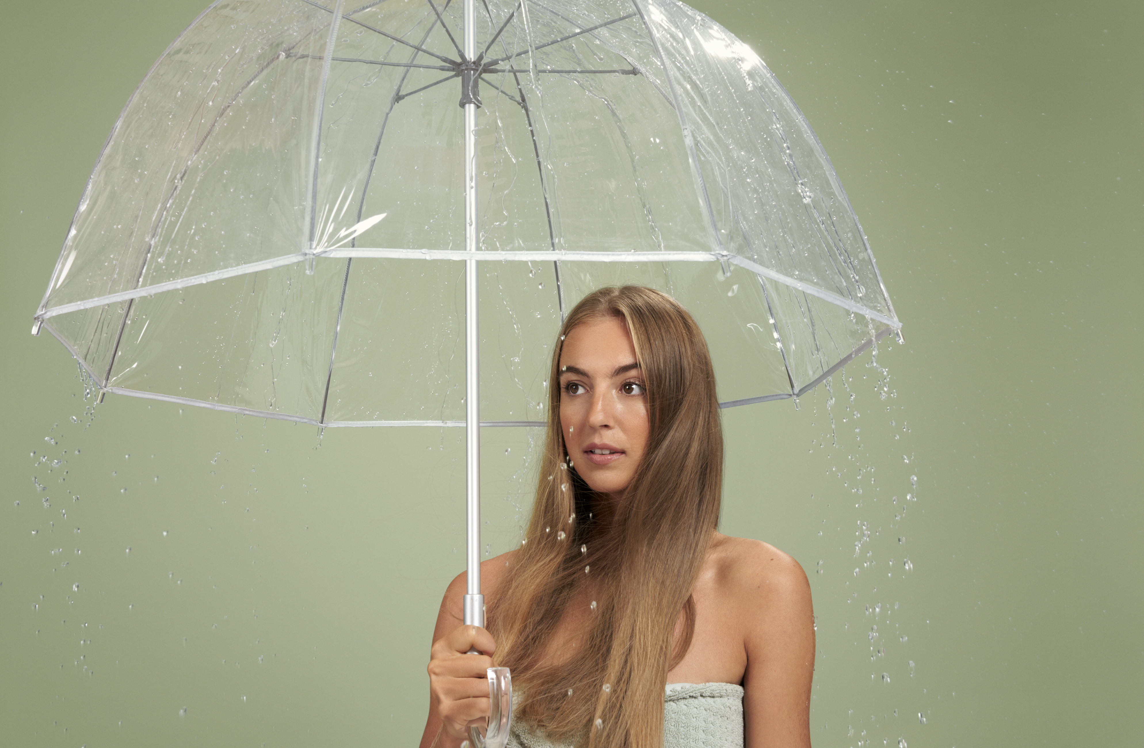 woman with long blonde hair holding a clear umbrella on a green background while rain falls down on her