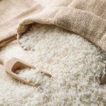 Rice in burlap sack and wooden scoop