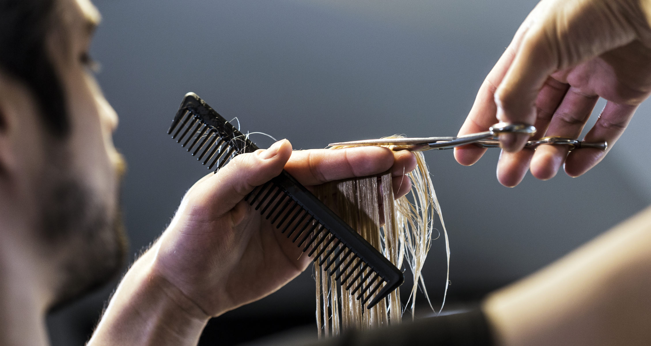 Stylist cutting a client's hair with scissors and a comb