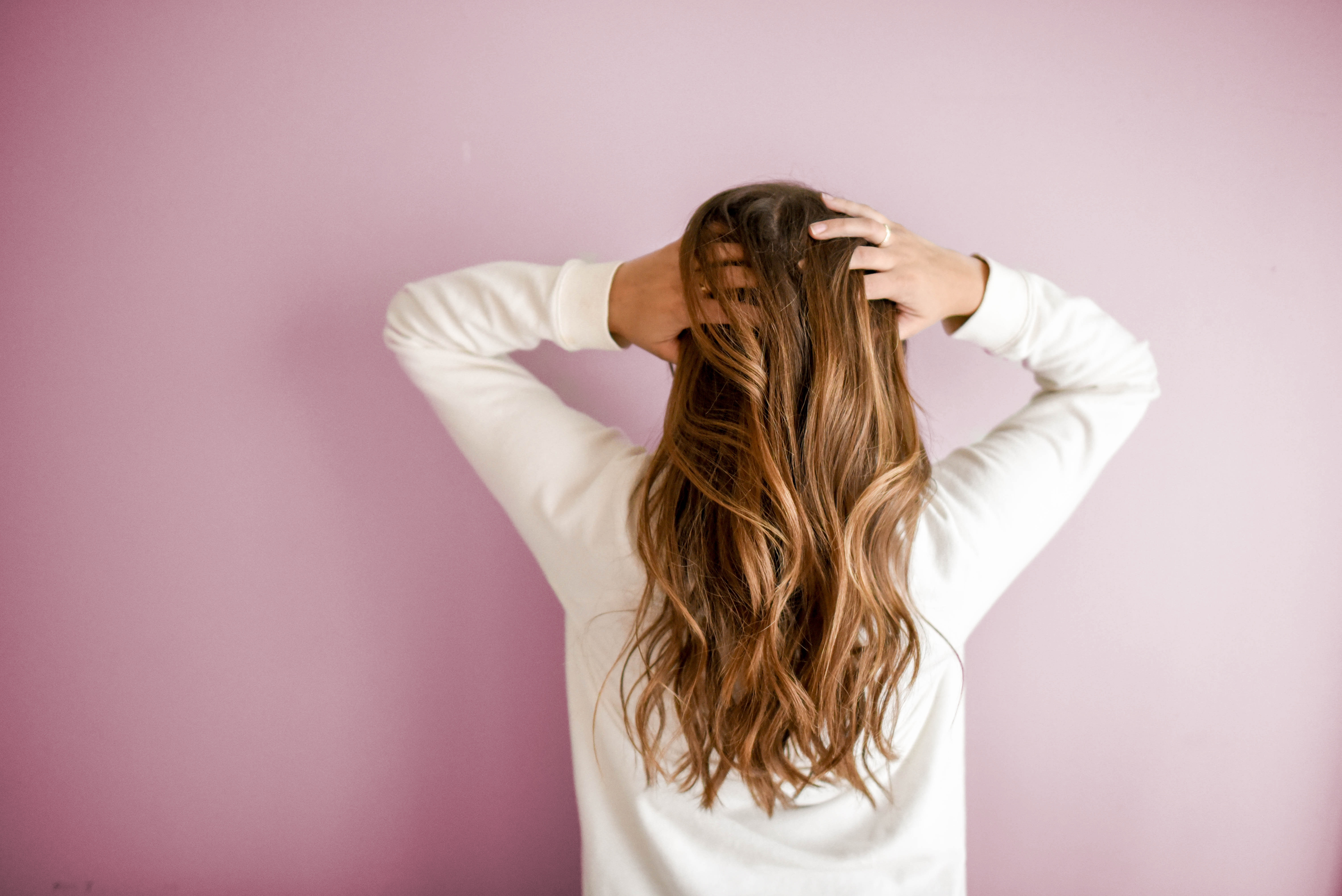 Woman with long brunette hair holding her head