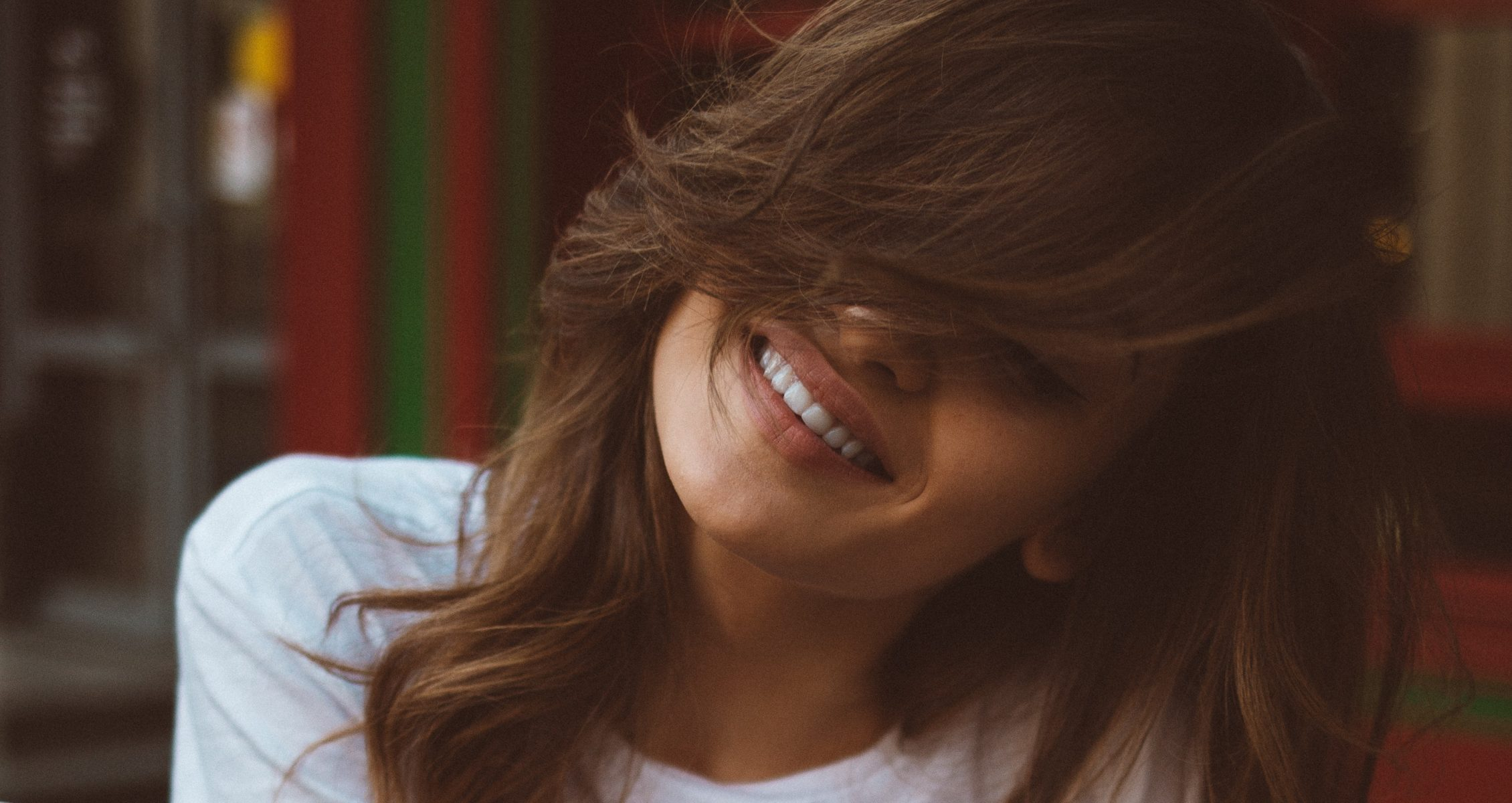 Woman with long bangs covering her face smiling
