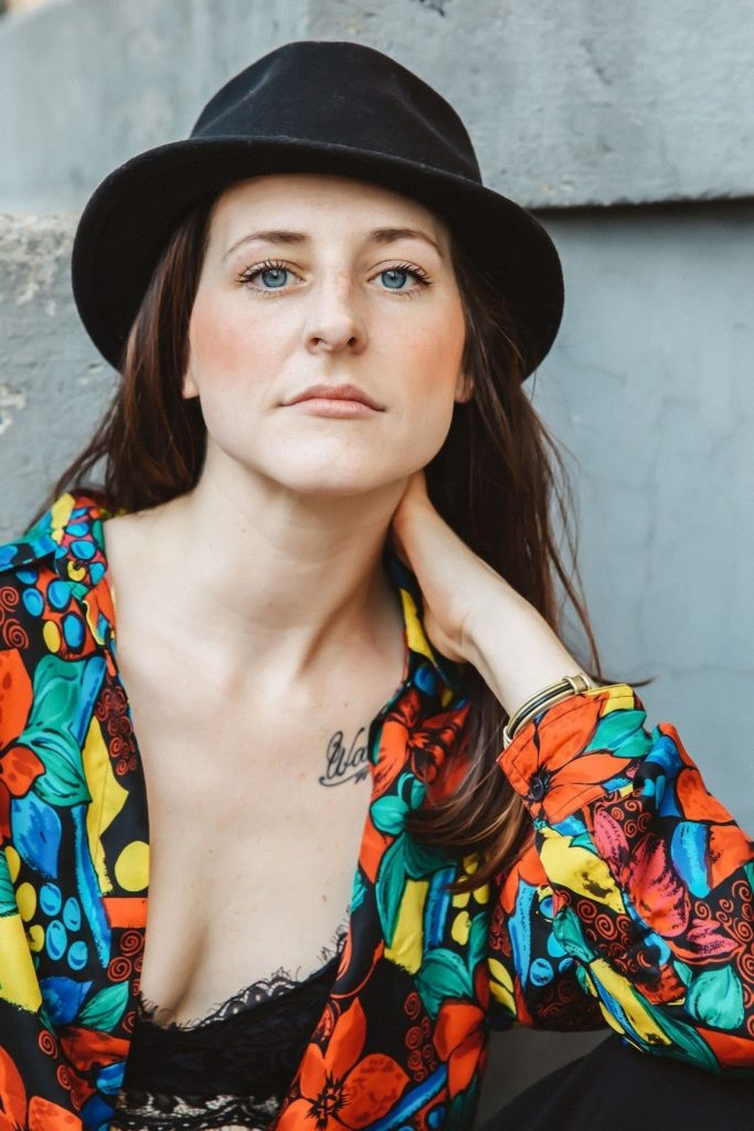 Pickthorn hair stylist Chelsey Pickthorn posing in a black hat and colorful floral blouse