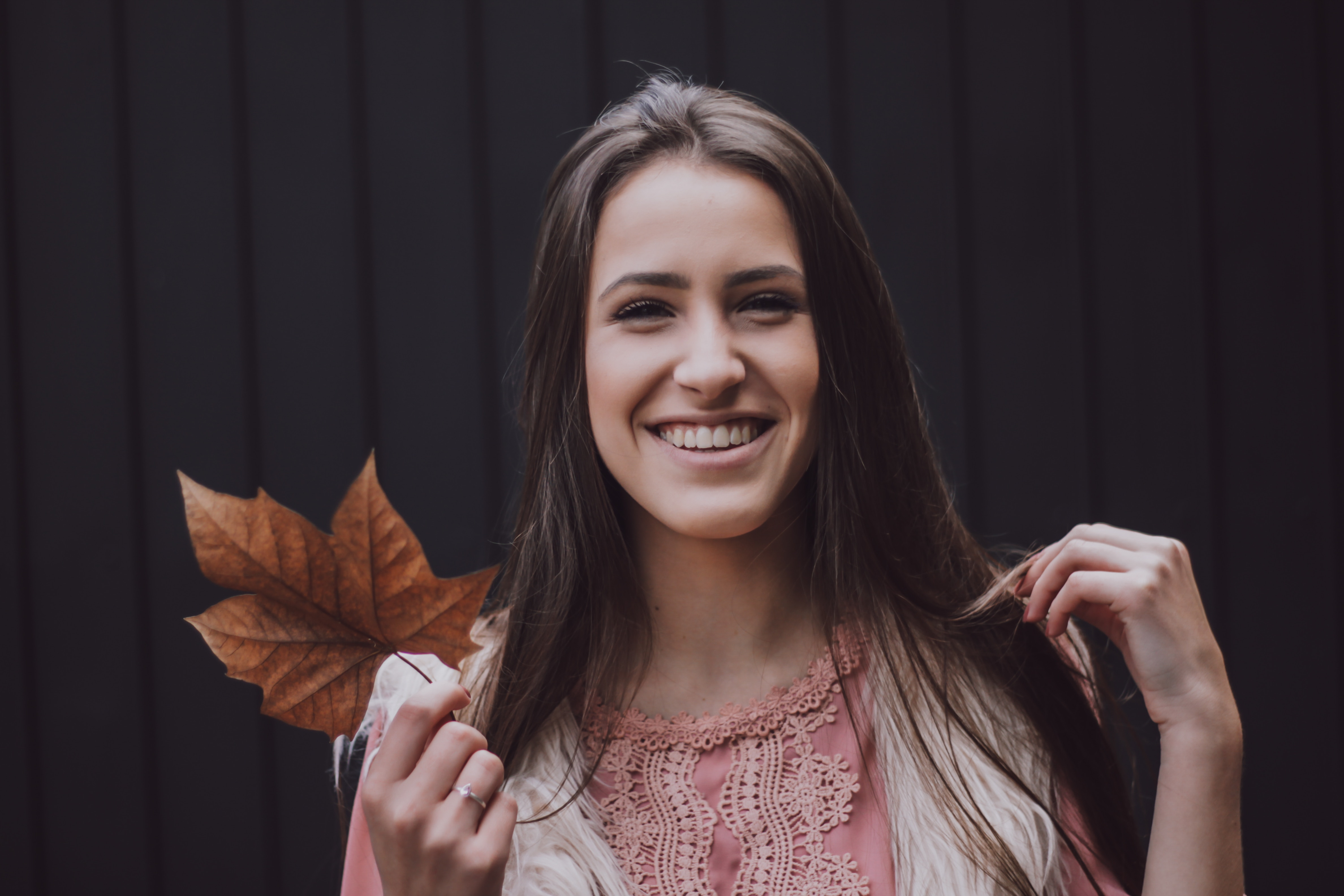 girl smiling while holding a leaf