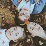 3 girls laying on fall leaves