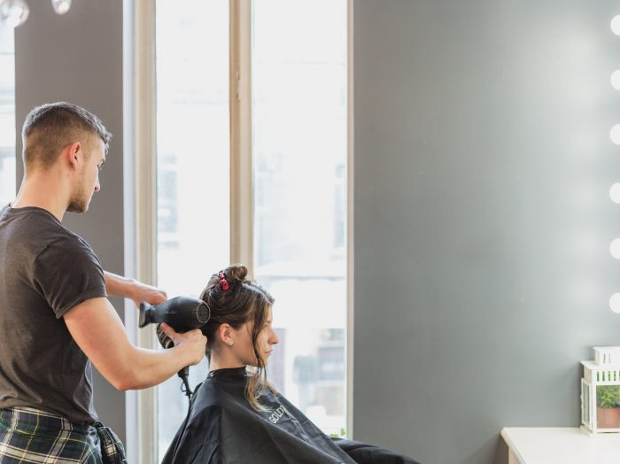male cutting a woman's hair at hair salon