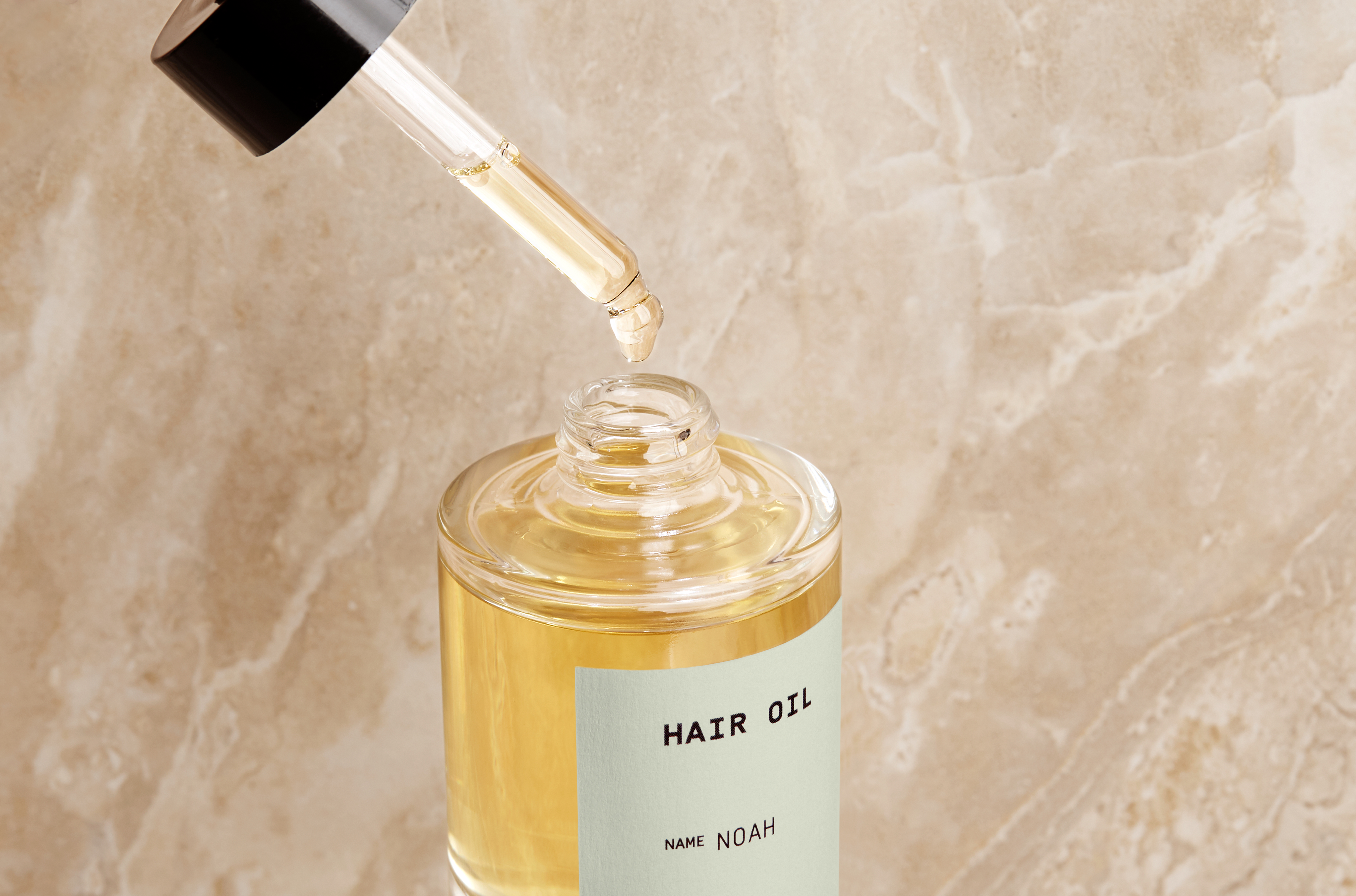 Custom hair oil in front of a marbled blush background