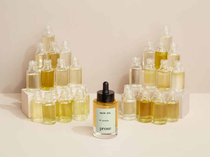 prose customized hair oil with natural oil ingredients behind it in glass bottles