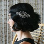 Side profile of a woman with short black curled hair and a feathered and embroidered black headband