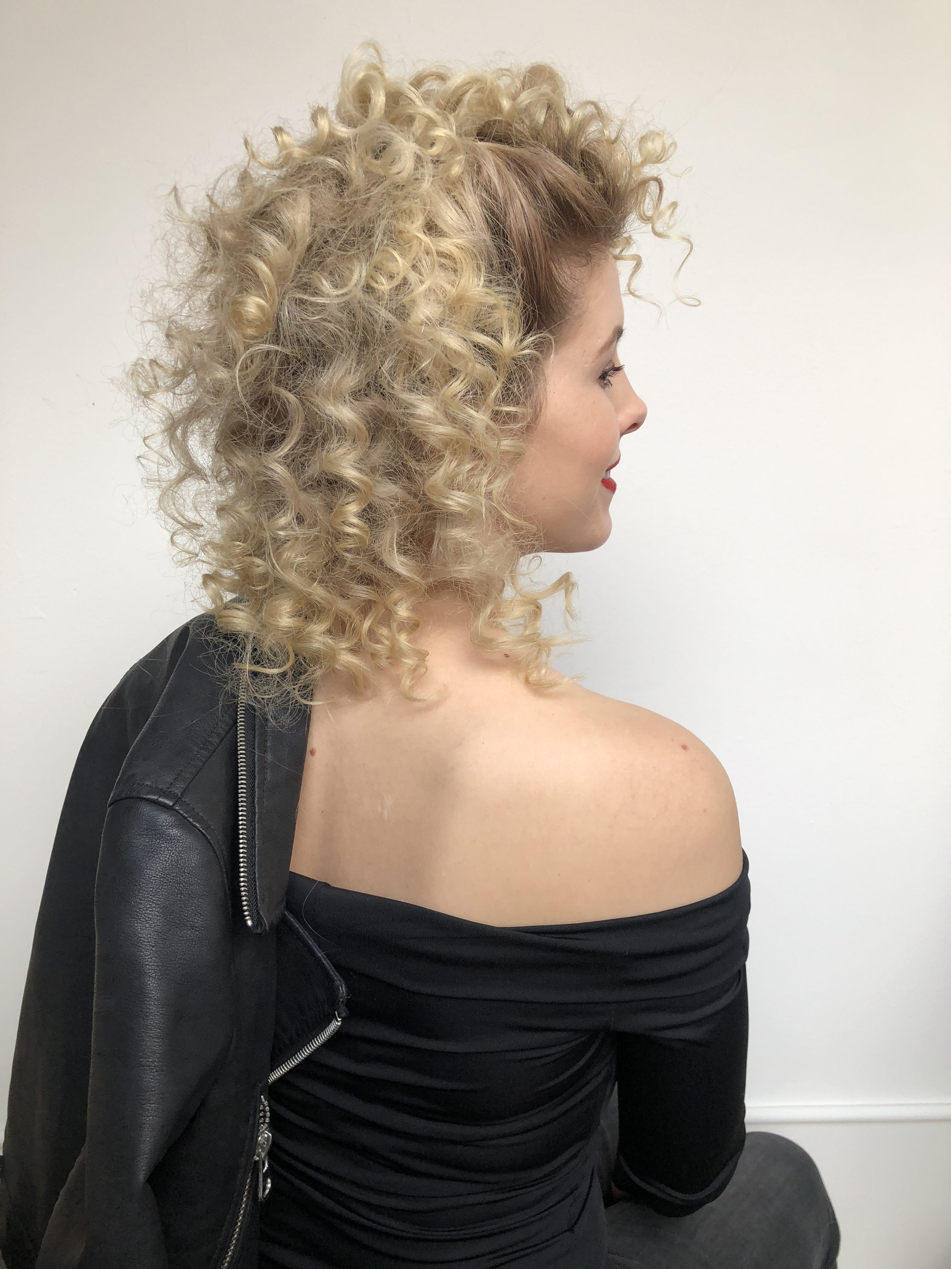 Sandy from grease hair tutorial on a blond woman wearing an off the shoulder black top and black leather jacket