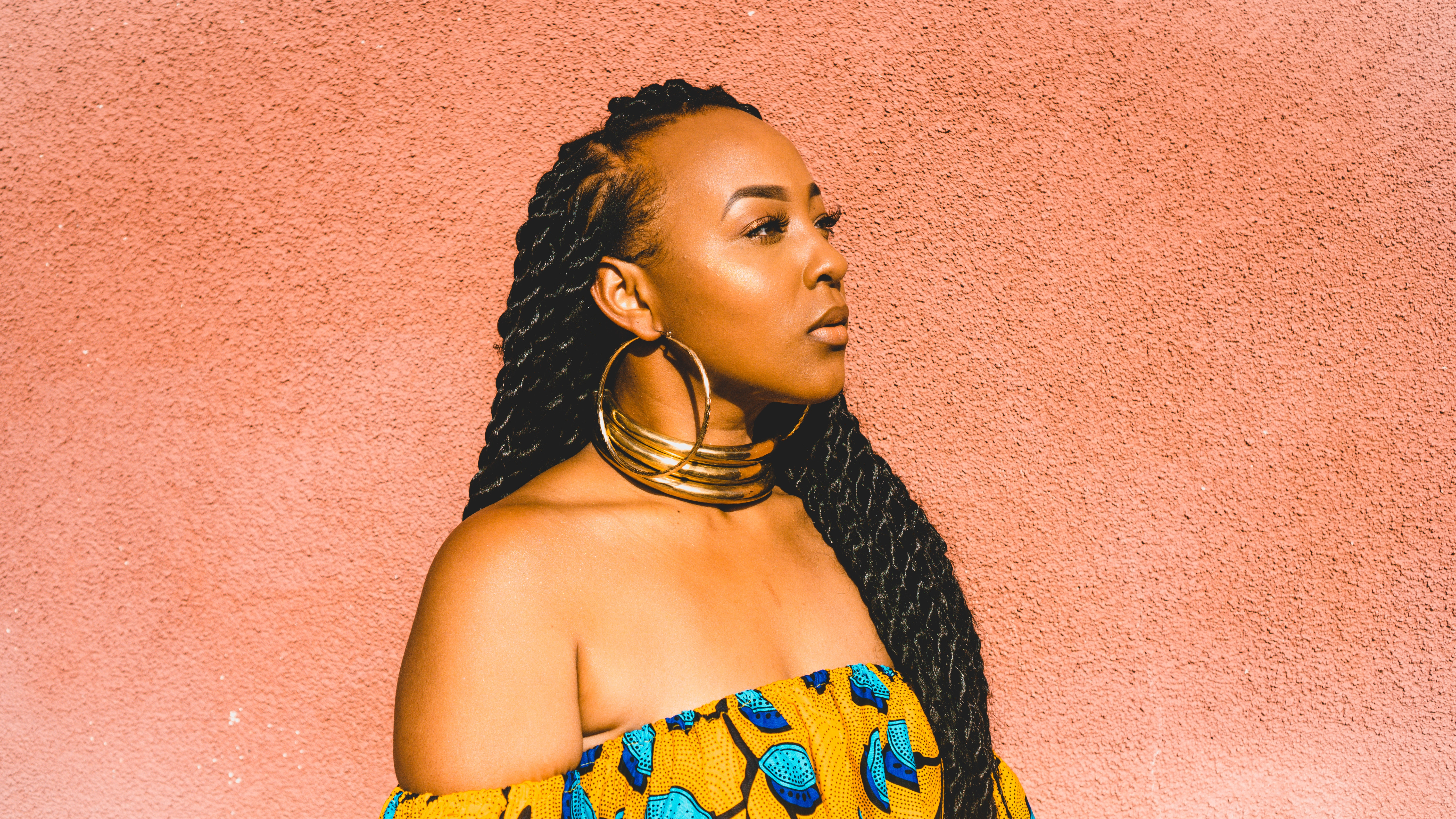 Woman with havana twists in her hair standing in front of a sorbet orange wall