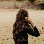Photo of the back of a brunette woman with long hair wearing a black sweater standing on a green lawn full of fall leaves