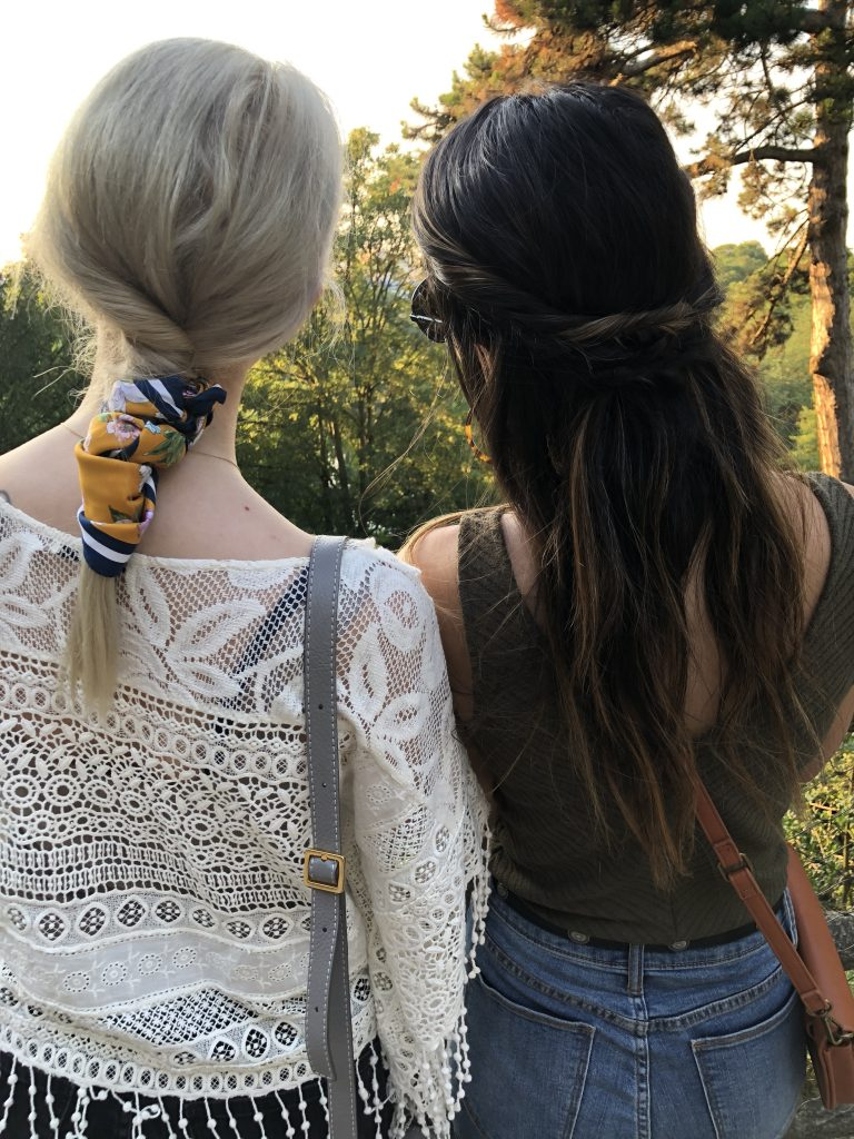 Two women posing in trending hairstyles. One poses with a low pony wrapped in a scarf and the other poses in a twisted half-up style.