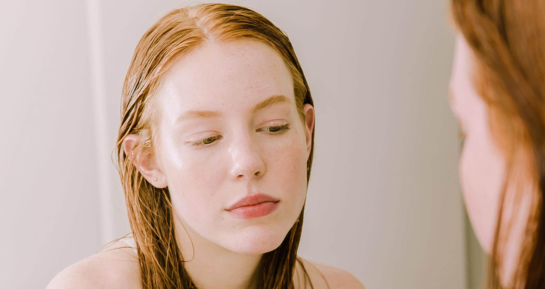 Woman with wet ginger colored hair observing her reflection in front of a bathroom mirror