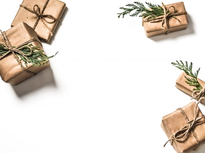 image of gift boxes wrapped in plain brown wrapping paper with twine ribbon and a pine leaf