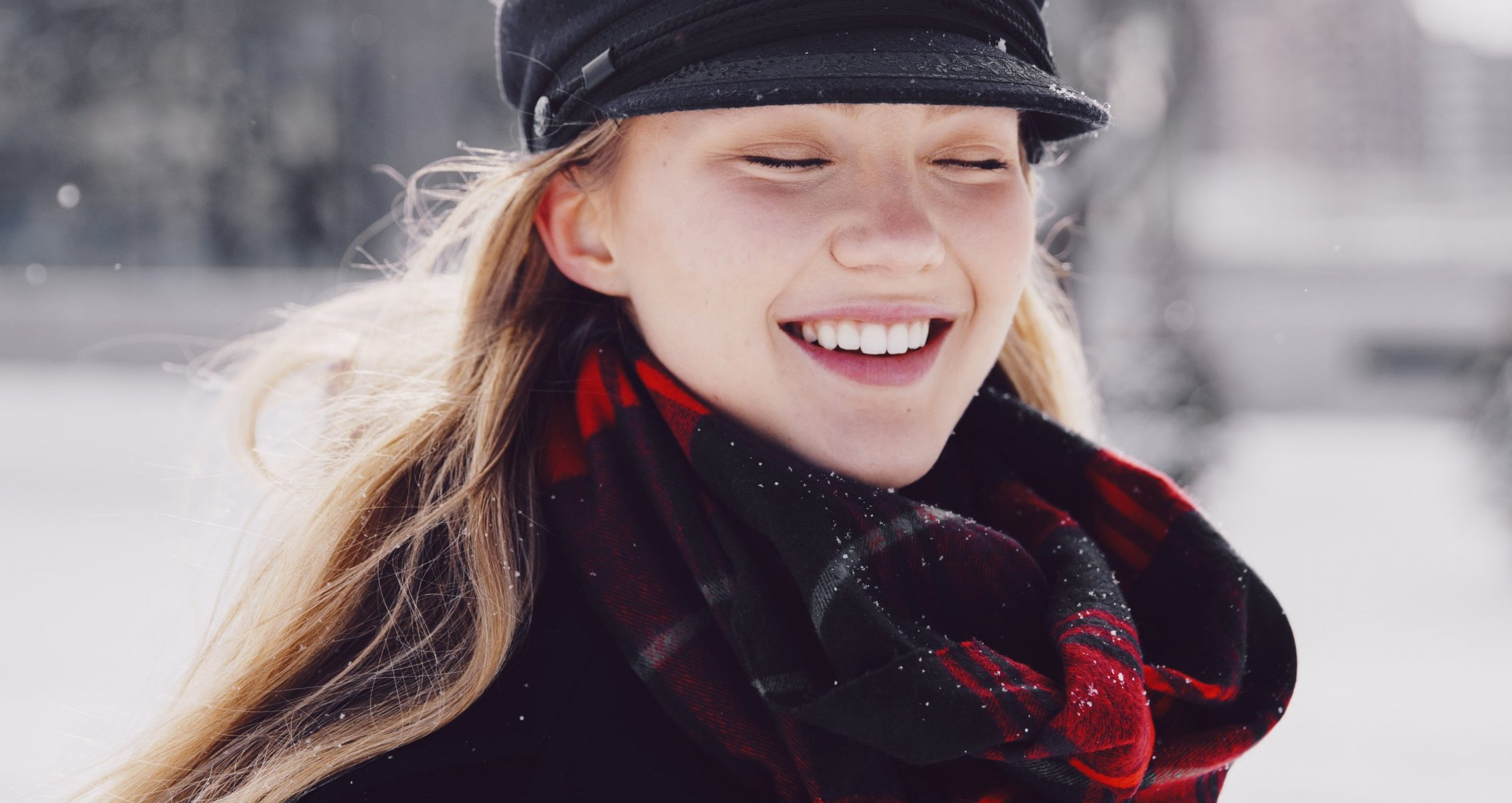 A blonde woman is smiling wearing a black hat, black coat, and red plaid scarf