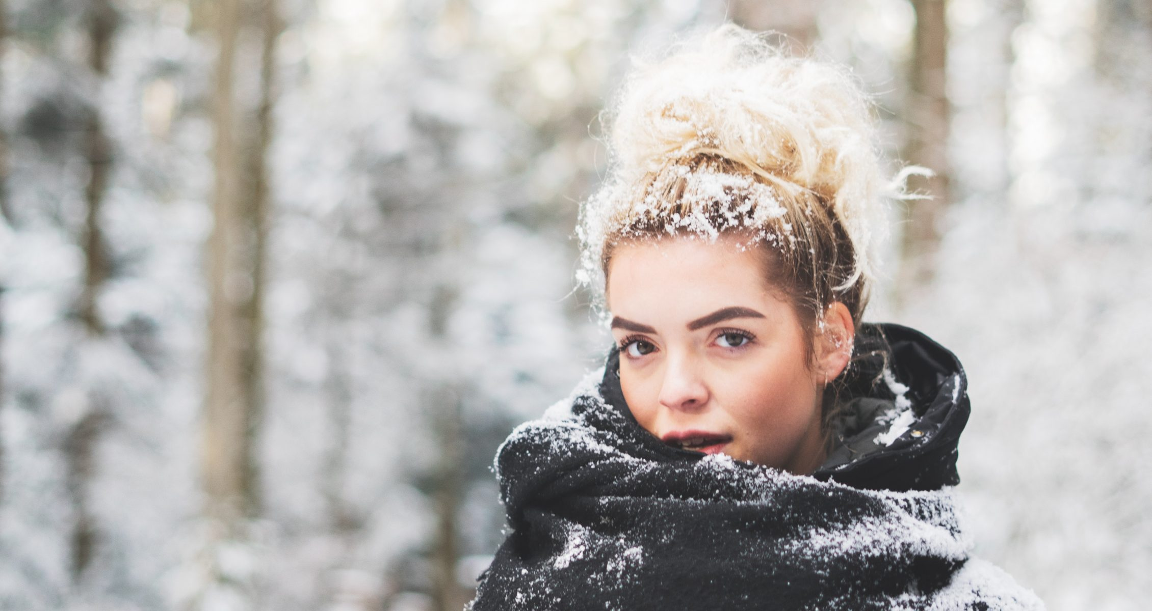 A blonde woman wearing a bun has snow on her hair and is standing in the snow covered woods wearing a large black scarf covered in white snow